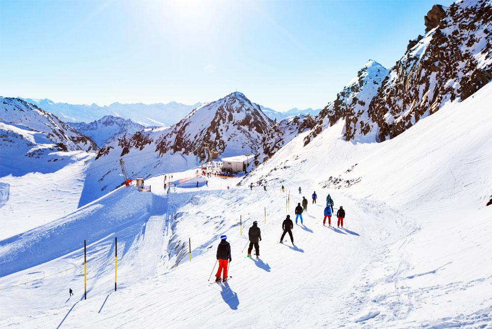 Personnes skiant sur une piste - location de matériel de sports d'hiver