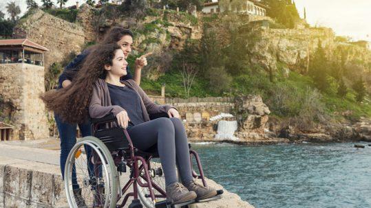 Femme sur un fauteuil roulant accompagnée par une amie