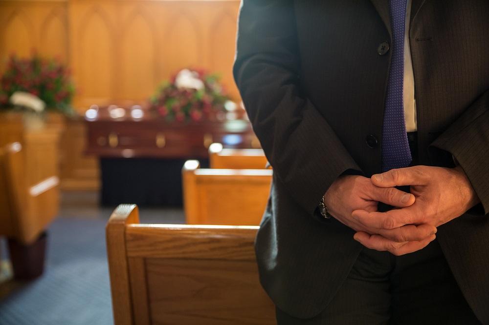 homme debout dans église mains croisées