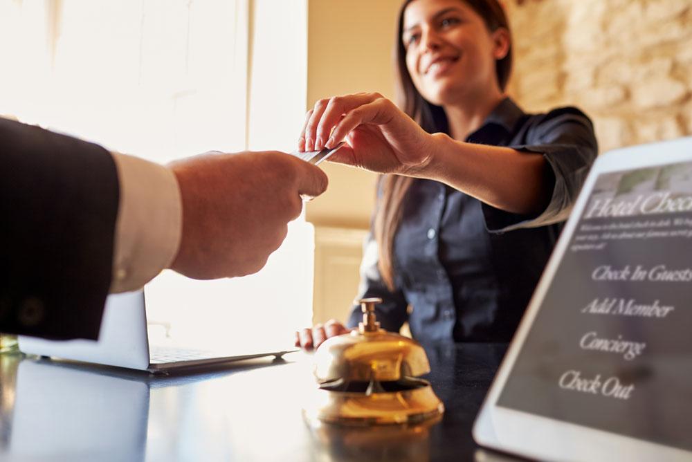 Jeune femme qui règle une prestation de service au comptoir d'un hôtel