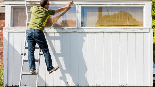 homme qui utilise une échelle pour repeindre la façade de son garage
