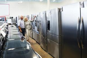 Un couple en train de regarder un réfrigérateur dans un magasin d'éléctro-ménager